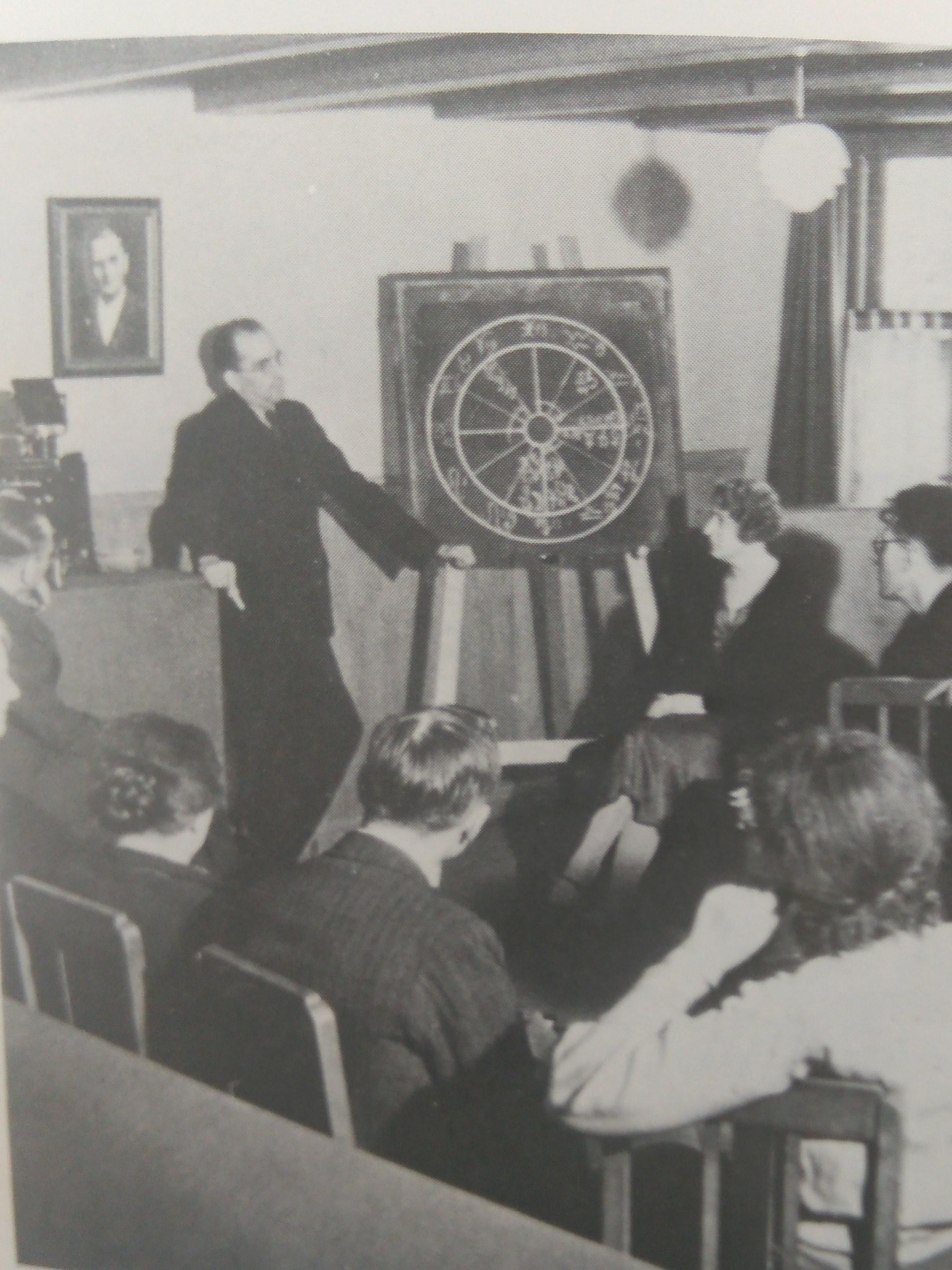 Rijckenborgh, dando una clase de lo que parece ser un curso de astrología, bajo el retrato de Heindel